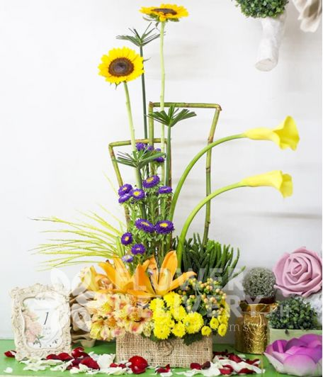 A Box of Mixed Yellow Flowers with Violet Mums